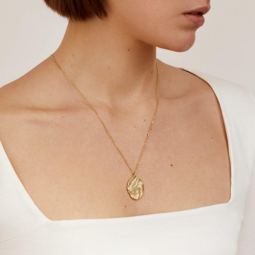 gold medallion necklace on model