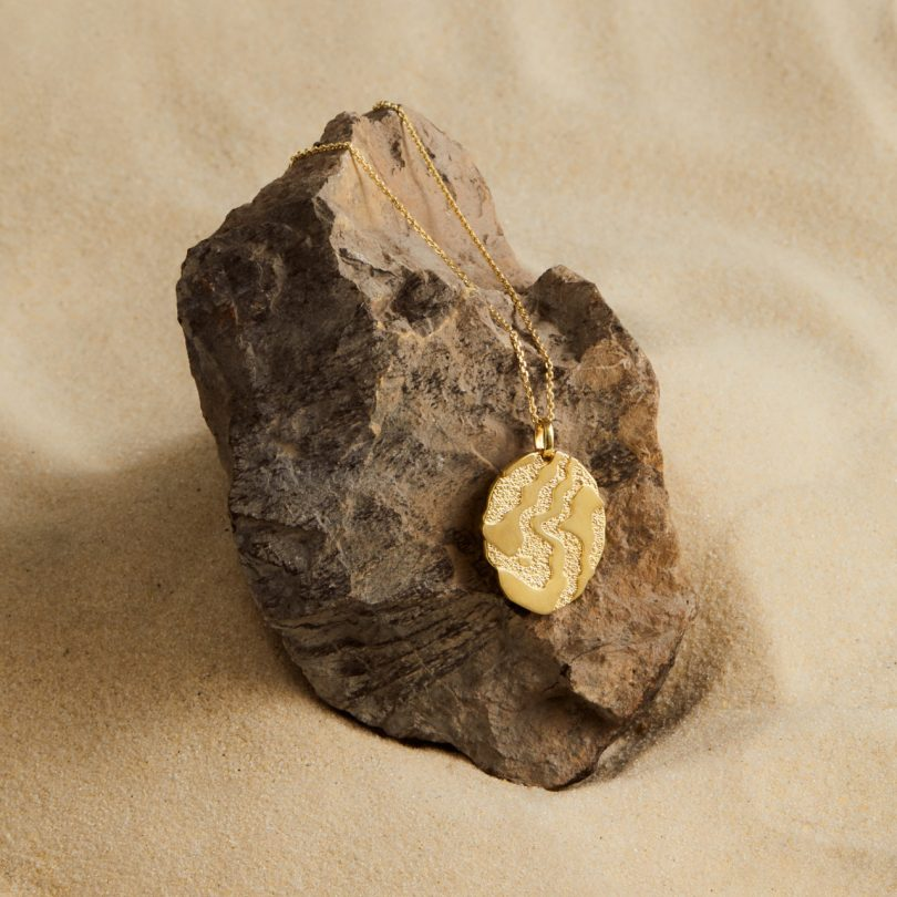 gold pendant necklace on rock