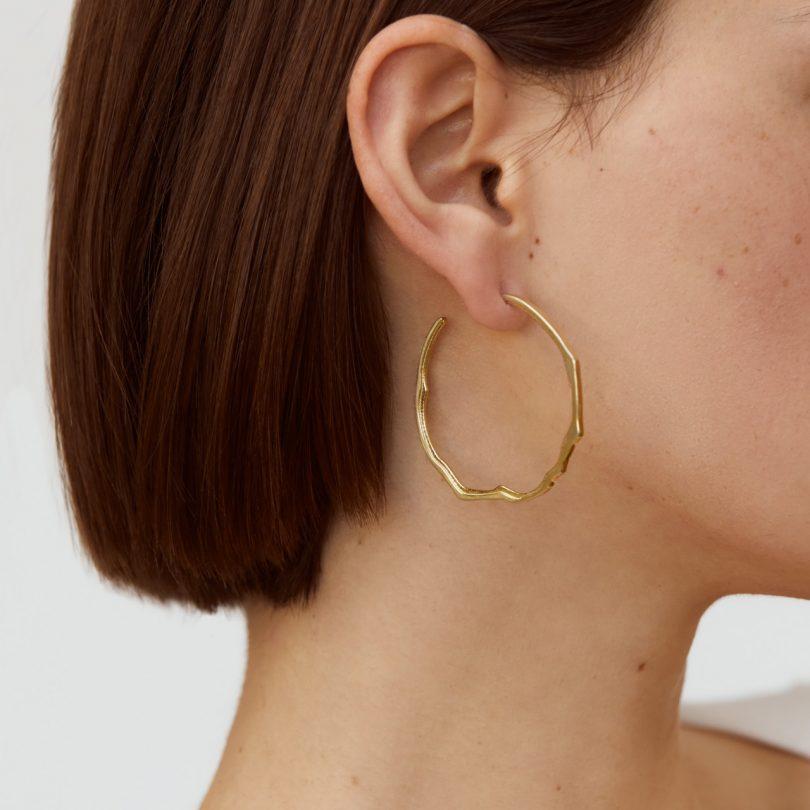 gold modern hoop earrings on model