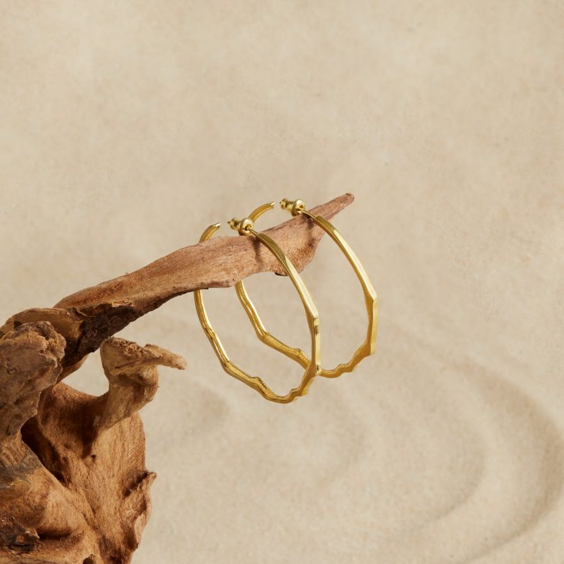 gold modern hoop earrings on wood
