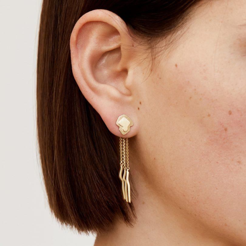 gold dangling earrings on model