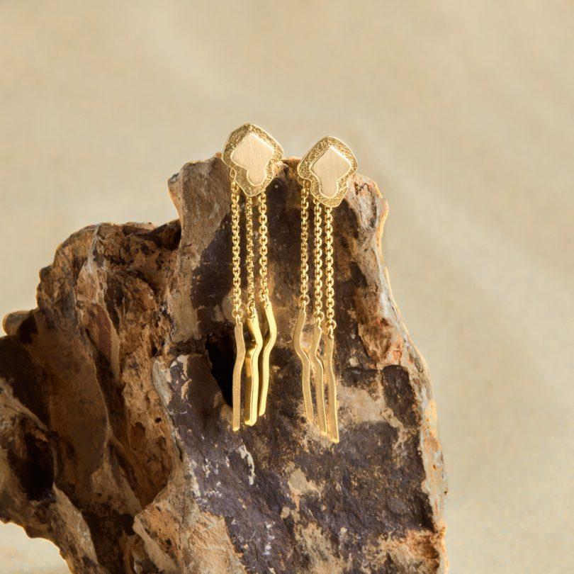 gold dangling earrings on rock