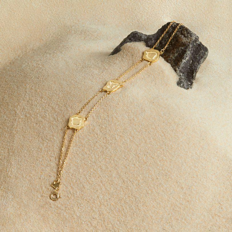 gold bracelet in sand on rock