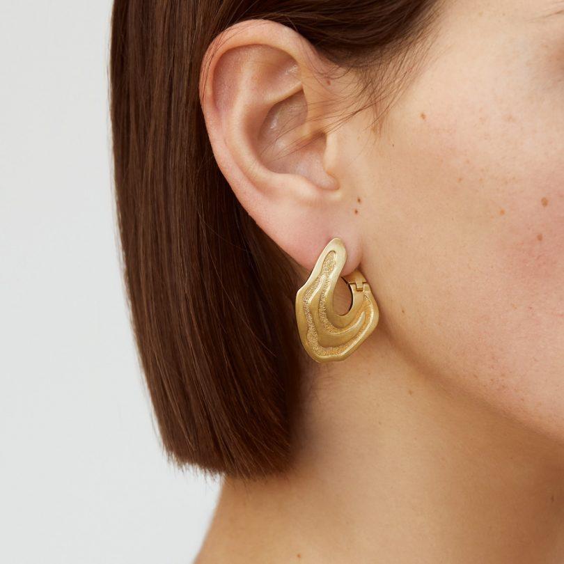 gold earrings on model