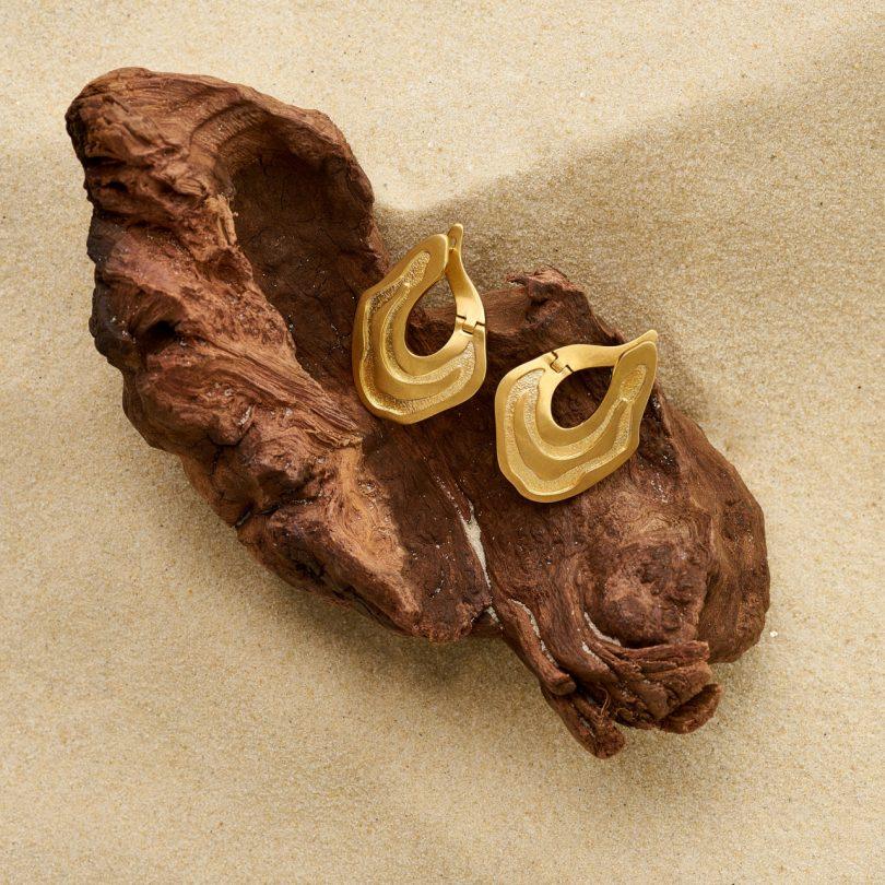 gold earrings on wood