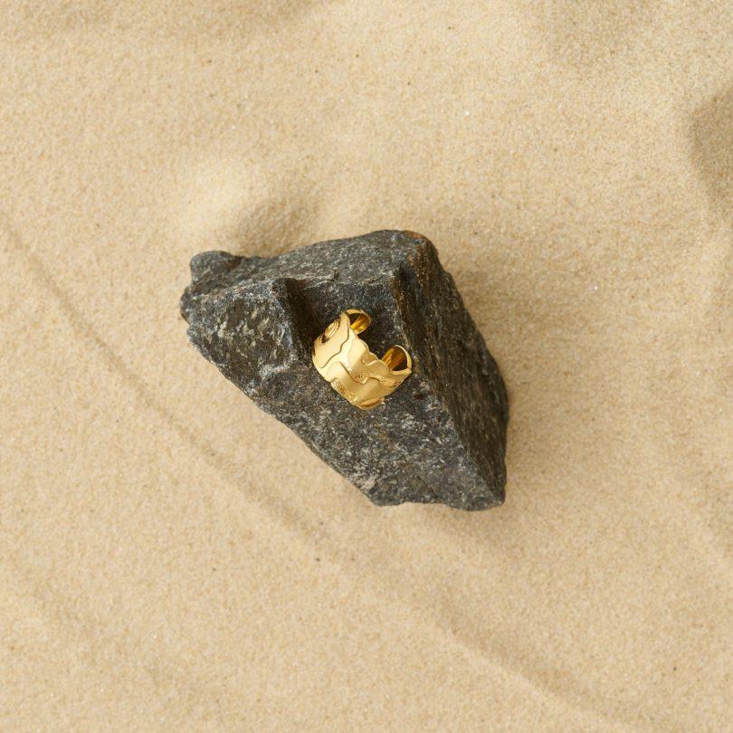 modern gold ring on rock