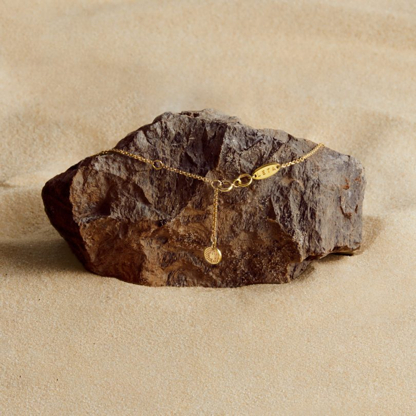 gold plated necklace on rock