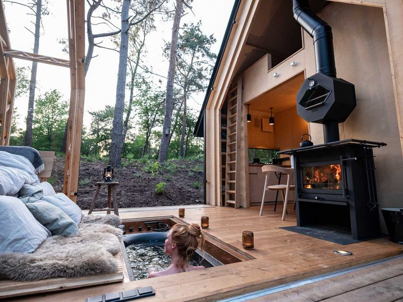 open roof cabin in the woods with girl in hot tub
