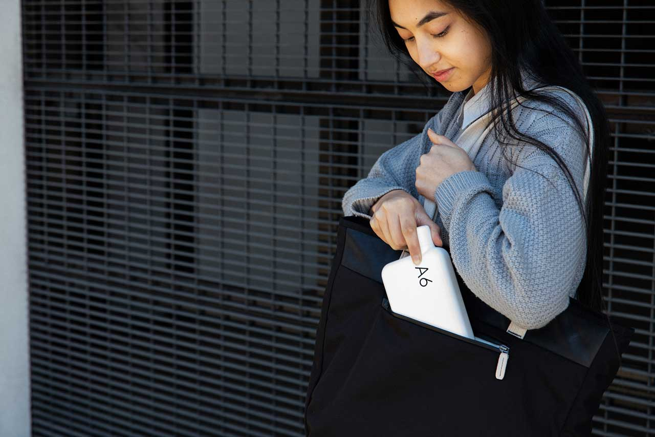 girl placing flat white water bottle in black bag