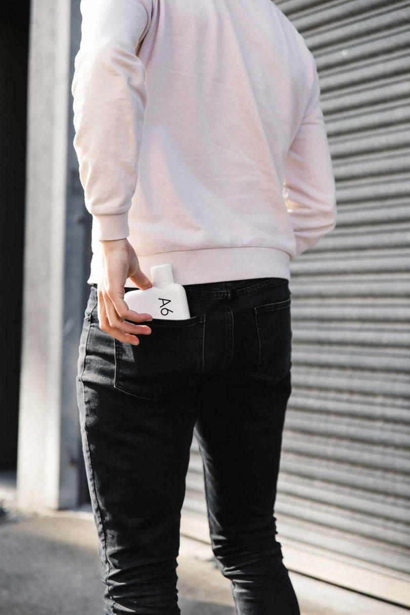 man putting white water bottle in back pocket
