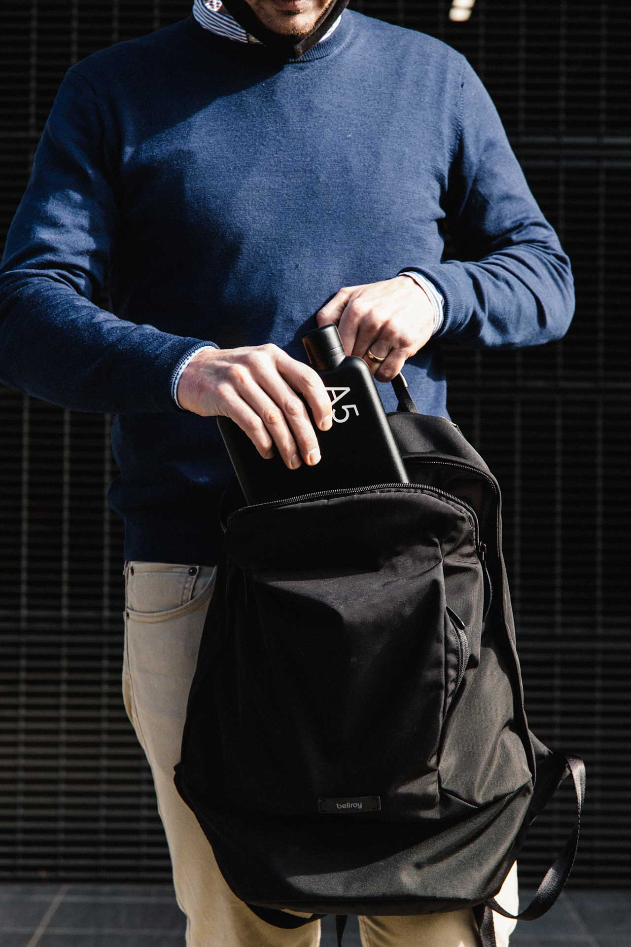 man placing flat black water bottle in backpack