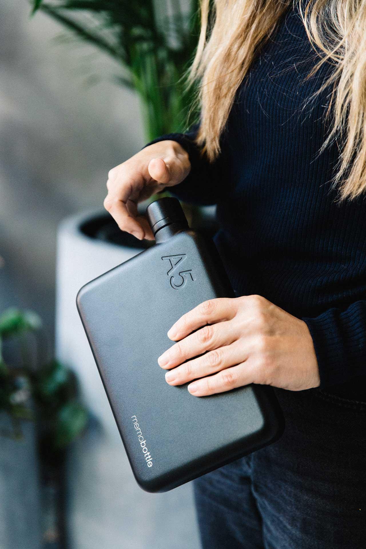 hands holding an A5 flat black water bottle