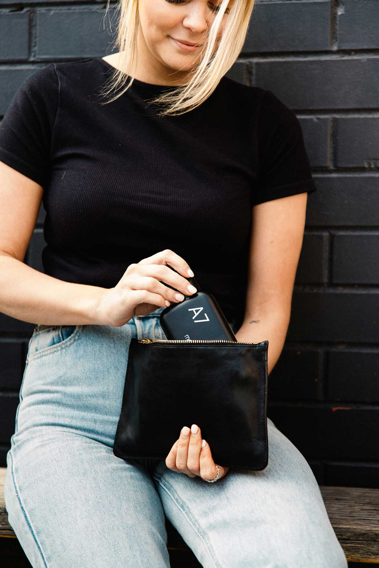 girl holding small flat black bottle with phone