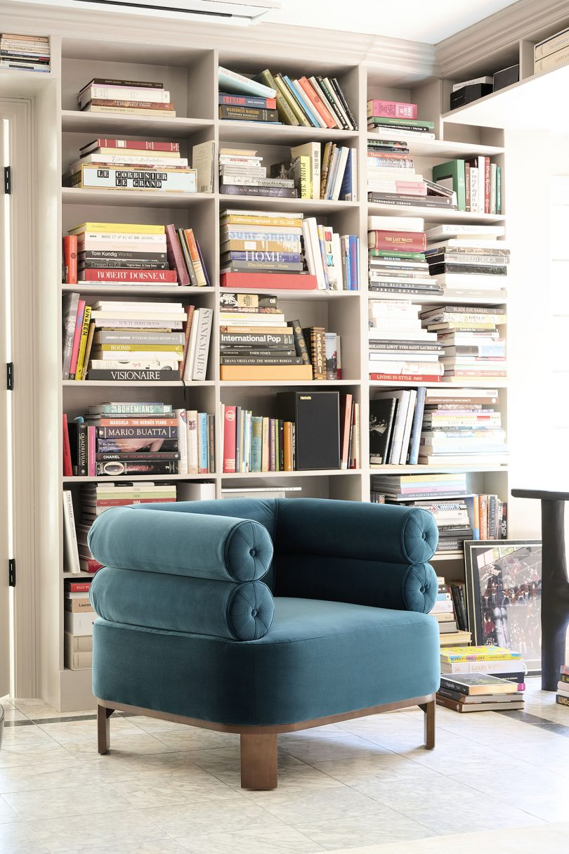 turquoise chair in front of large bookcase