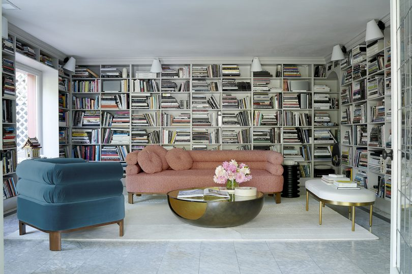 pink sofa, turquoise chair, white bench, and coffee table in light room with a wall of books