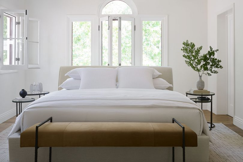 bright white bedroom with bed and bench