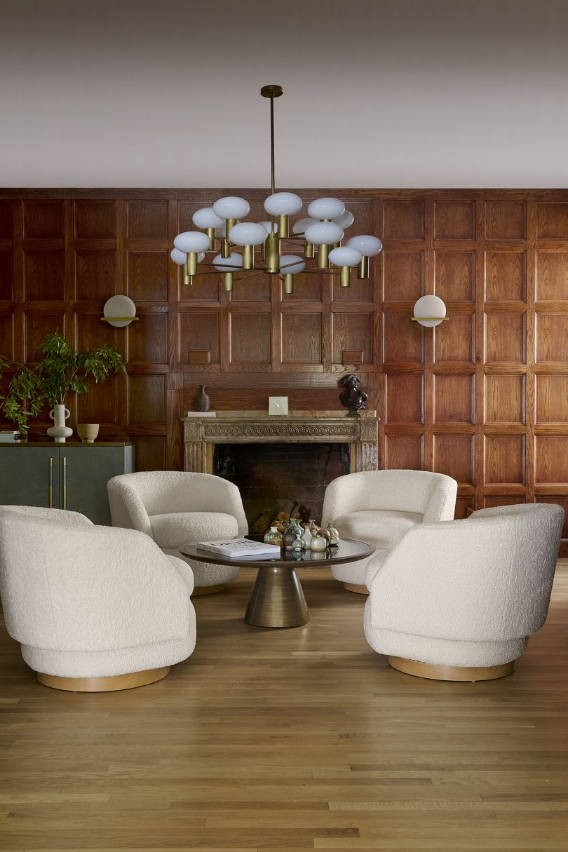 found white swivel chair surrounding a low table in a wood paneled room with a fireplace and large light fixture