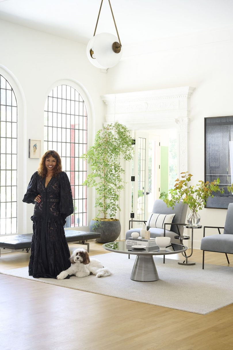 brown skinned woman in a long dress standing in a furnished interior space with a dog at her feet