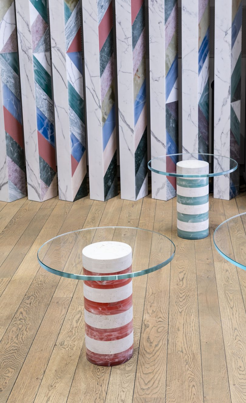 two striped tables with round glass tops in front of mural