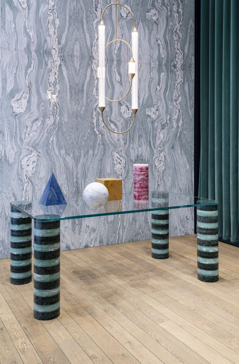 rectangular table with striped legs and glass top, lighting pendant, mural