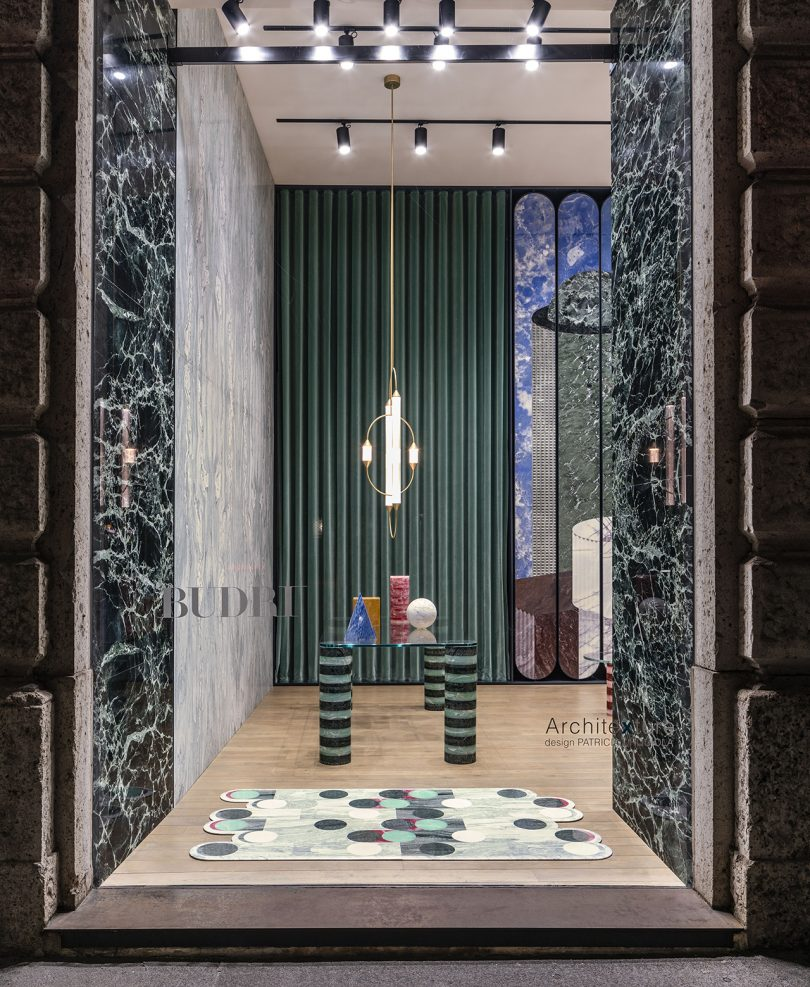 building entrance with dark patterned walls, rectangular table, lighting pendant