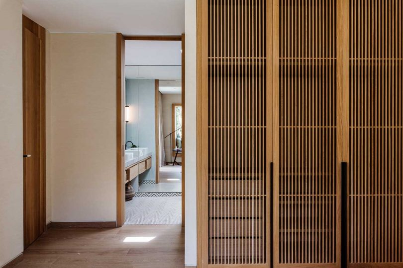 view into large modern bathroom with wooden closets