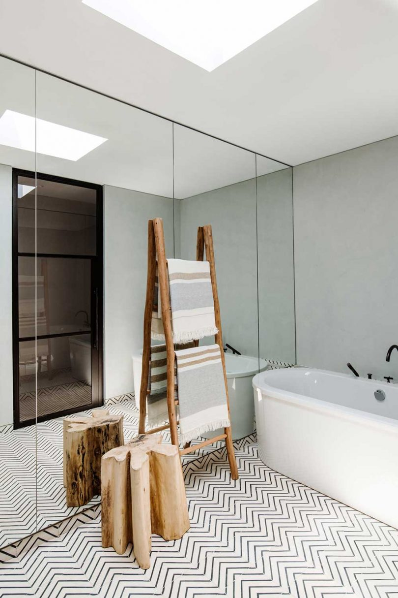 modern bathroom with mirrors and white tub