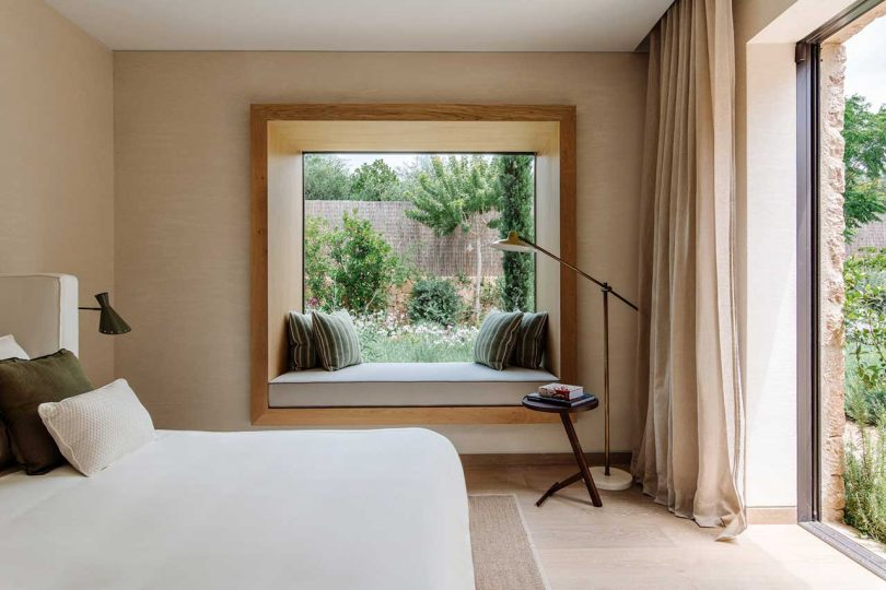 modern bedroom with white bedding and window with seat