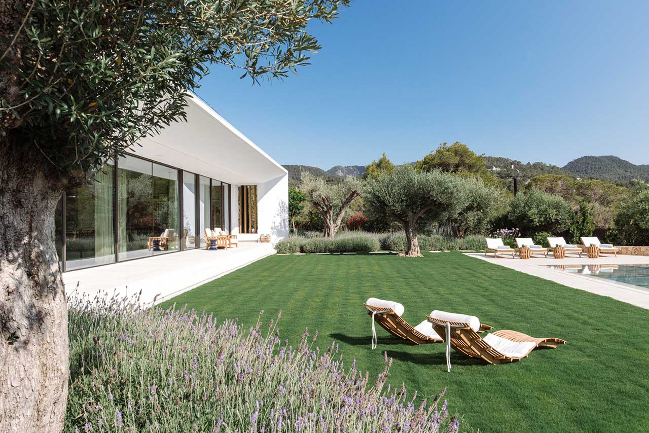 backyard view with green grass and lounge chairs beside a modern white house
