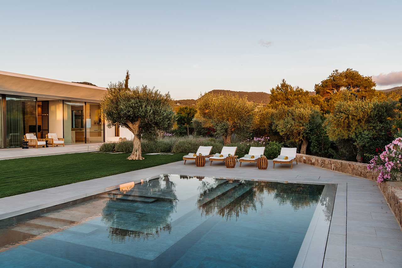evening view of swimming pool and back of house