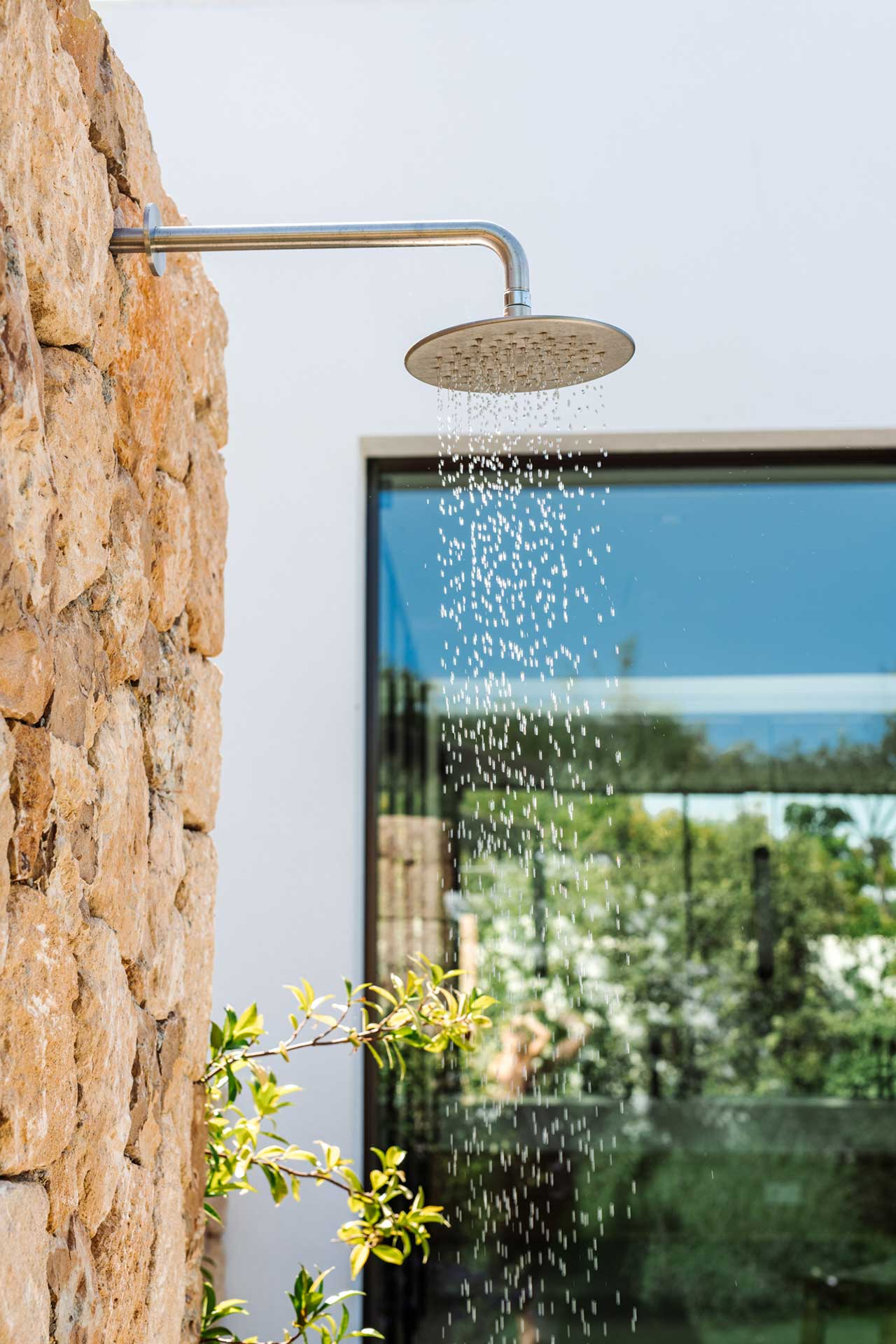 outdoor shower against stone exterior wall