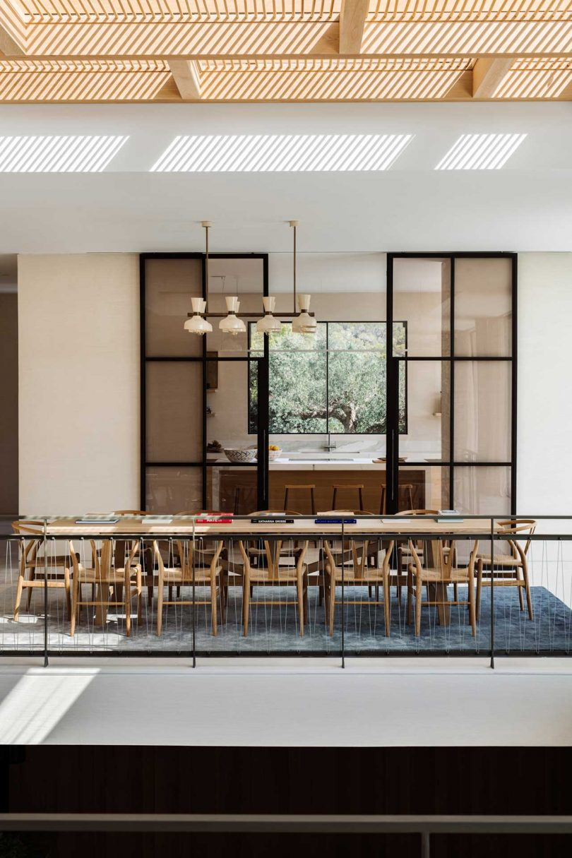 modern dining room looking into kitchen through glass doors