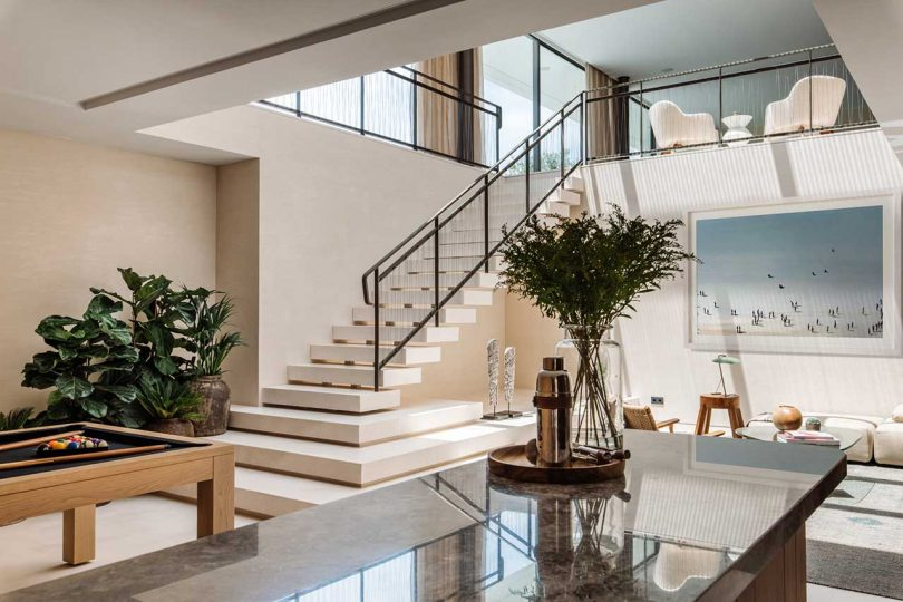modern living space with double height ceilings and staircase