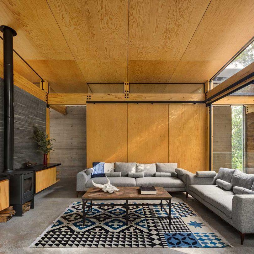 Interior de una casa moderna con techos y paredes de madera y muebles neutros