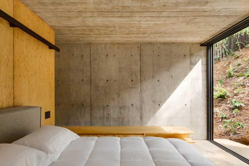Dormitorio moderno con paredes de hormigón y cama.