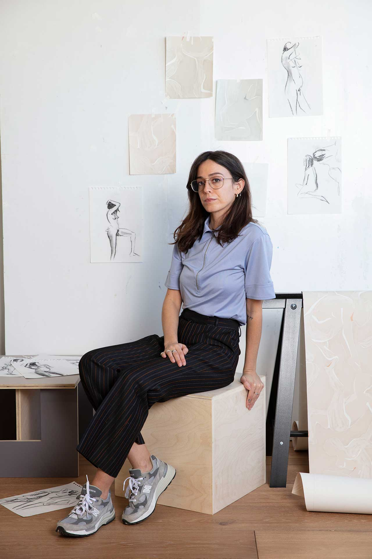 Person sitting on wood cube with sketches on wall behind them