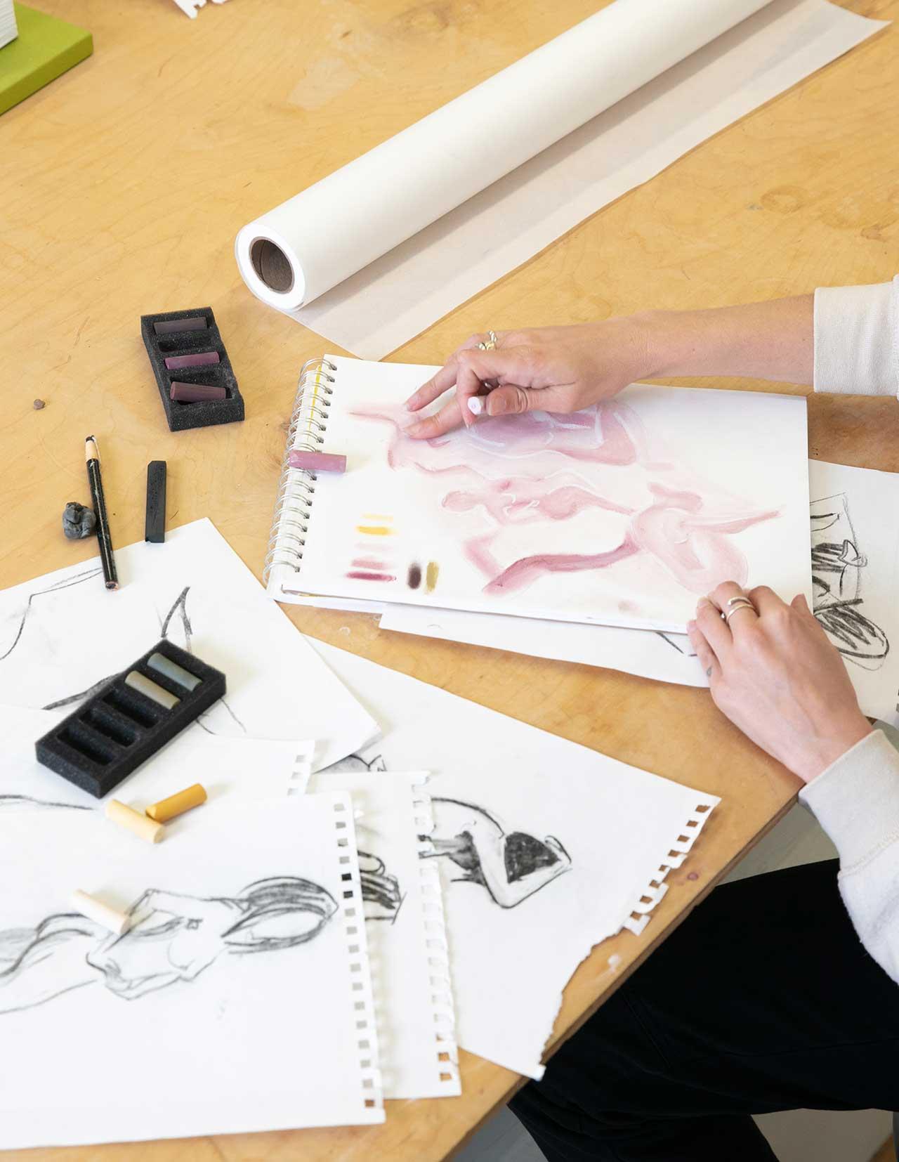 artist's hands sketching on paper