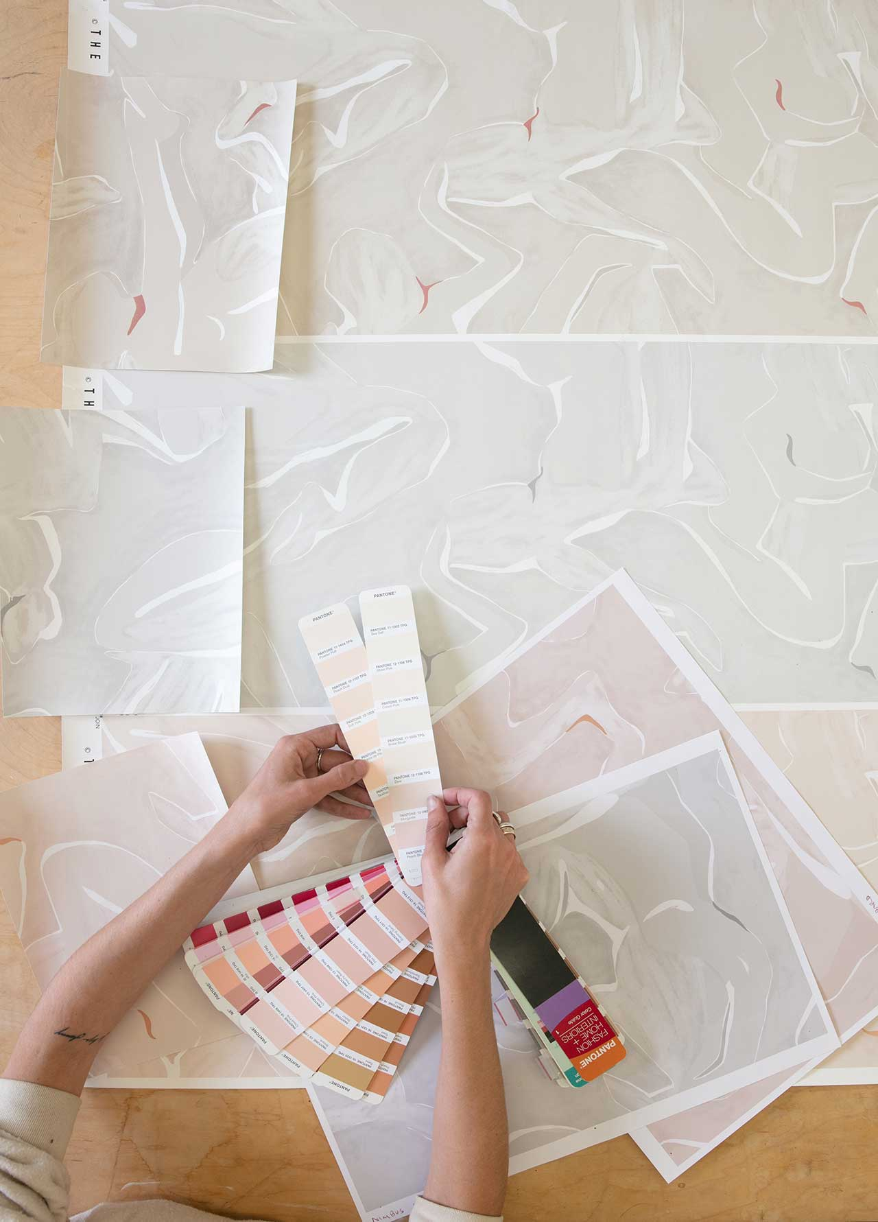artist's hands holding paint chips over abstract drawings