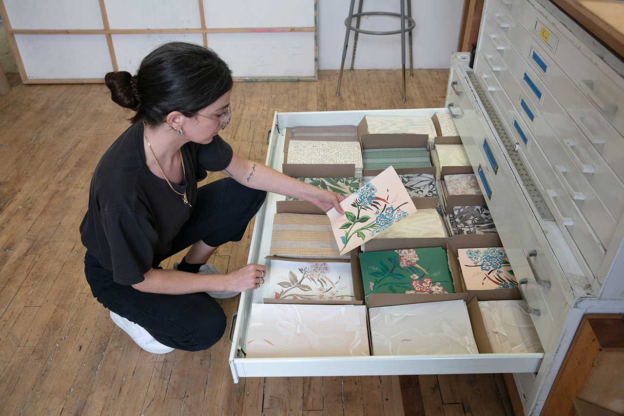 artist viewing wallpaper samples from a drawer