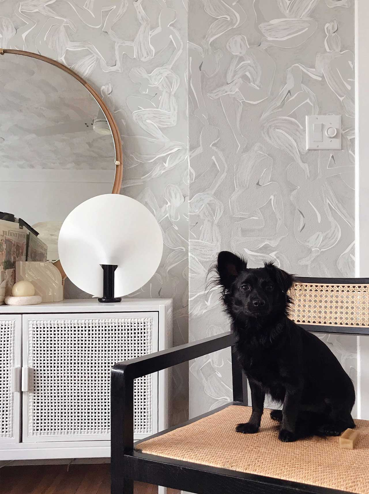room with pale gray abstract wallpaper with dog sitting on chair
