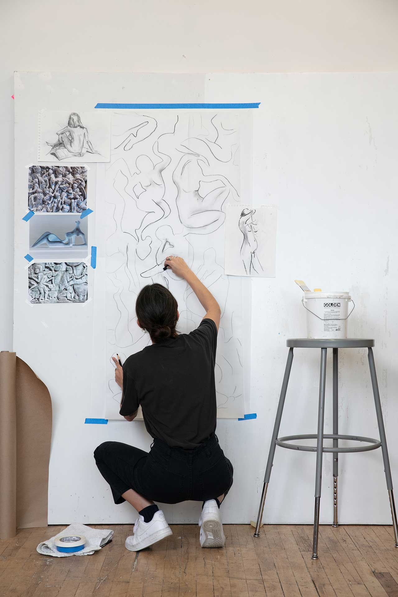 artist squatting down and sketching abstract pattern on wall
