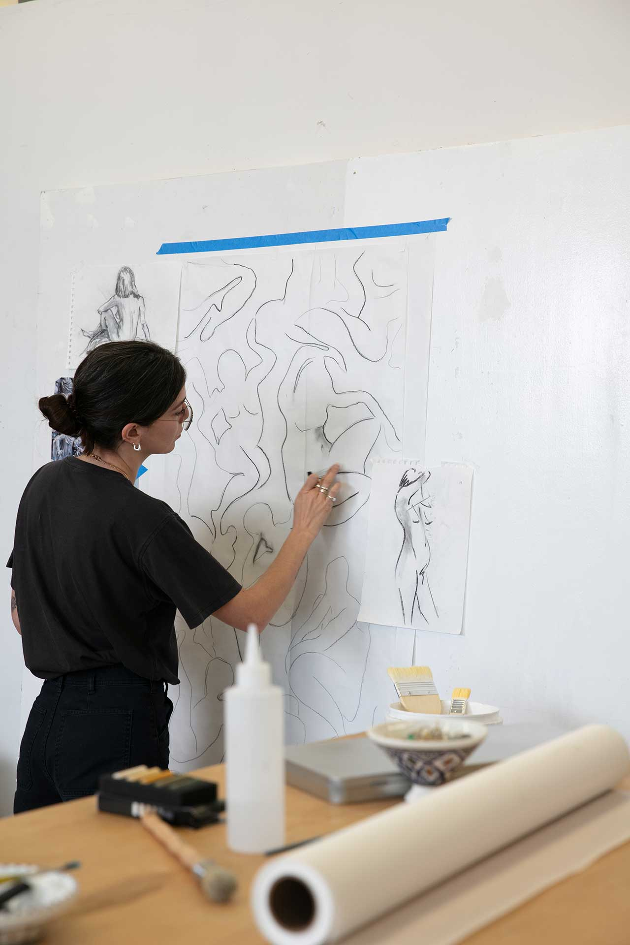 artist sketching on paper taped to a wall