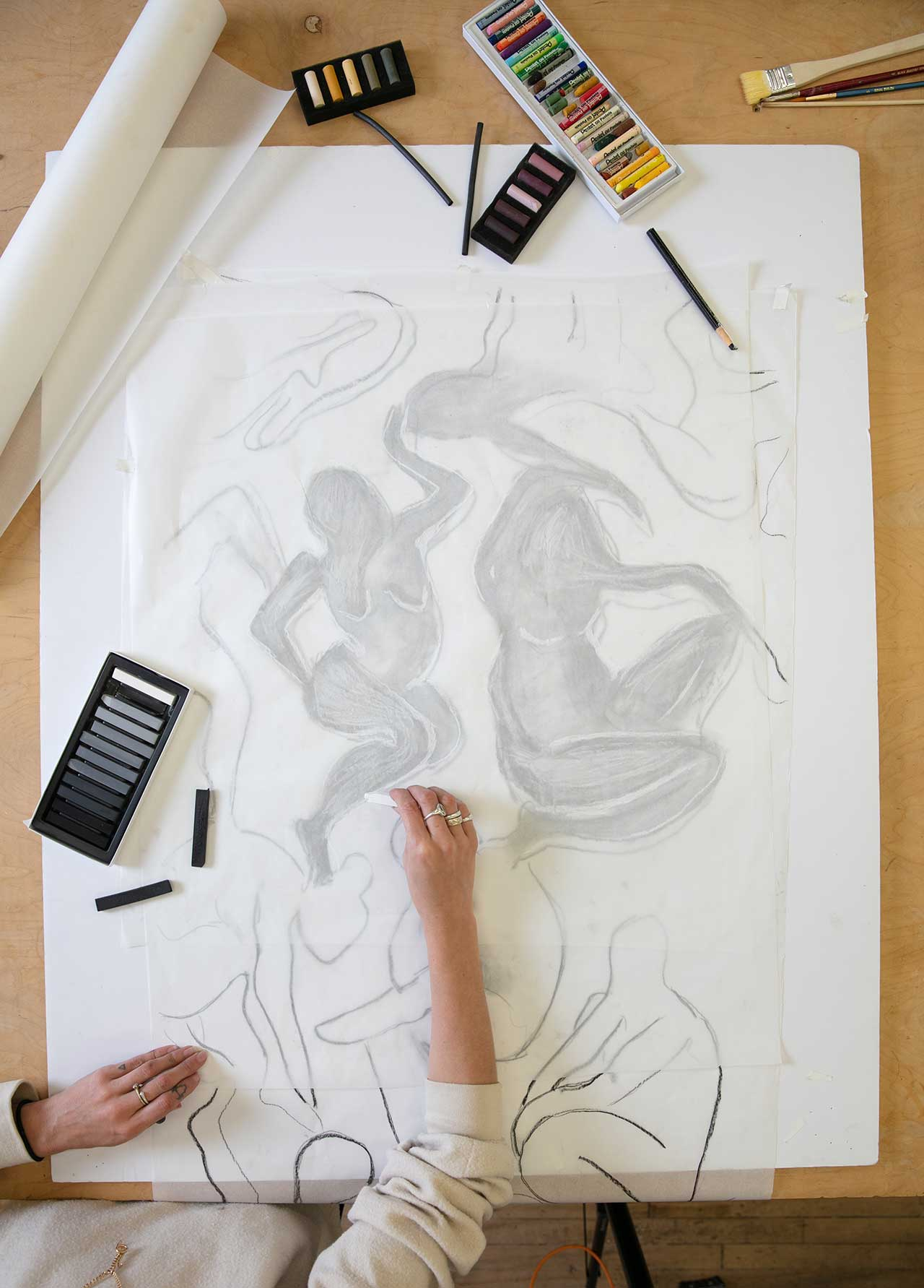 artist preparing layout of drawing over tracing paper