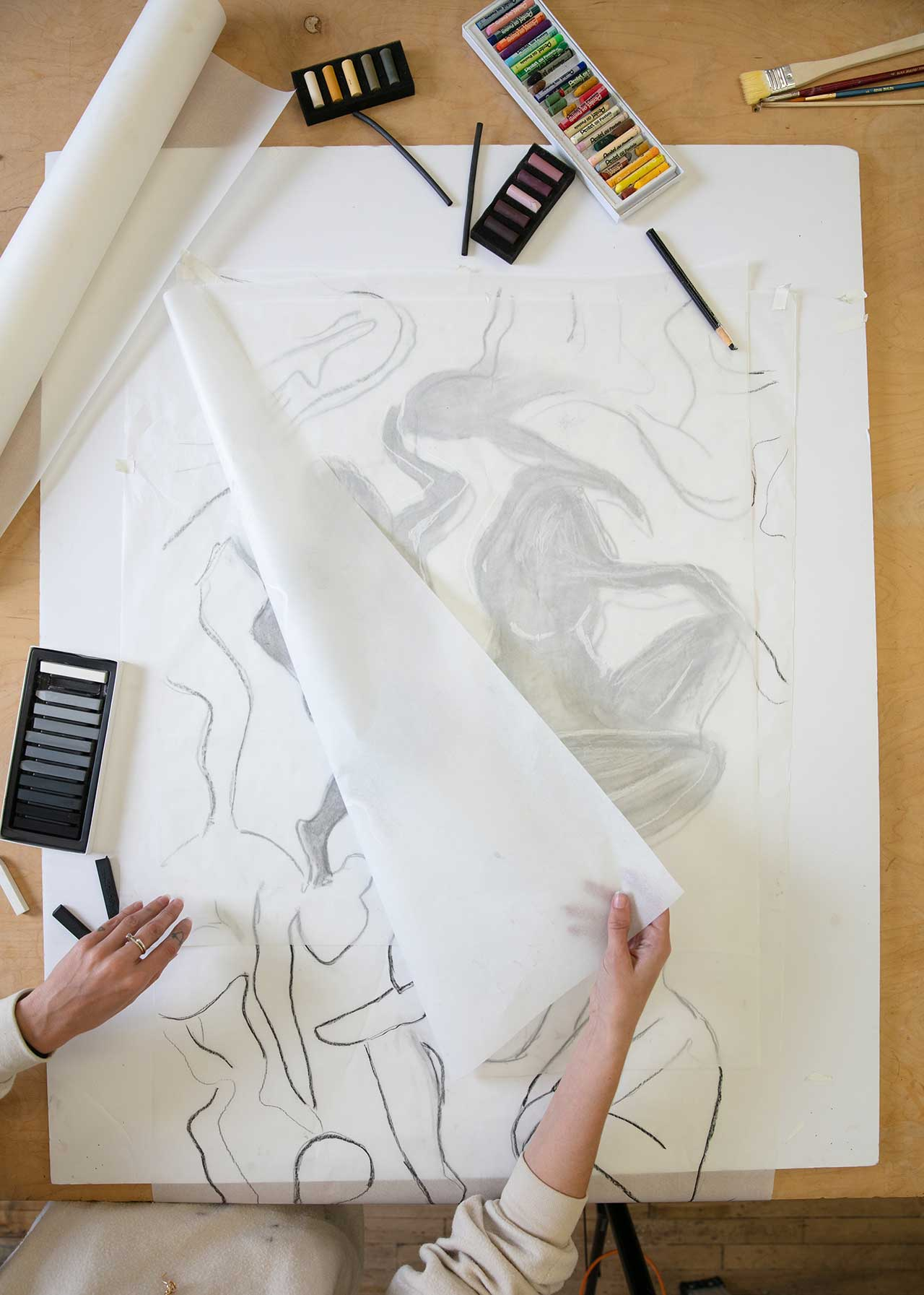 artist inspecting abstract drawing through trace paper
