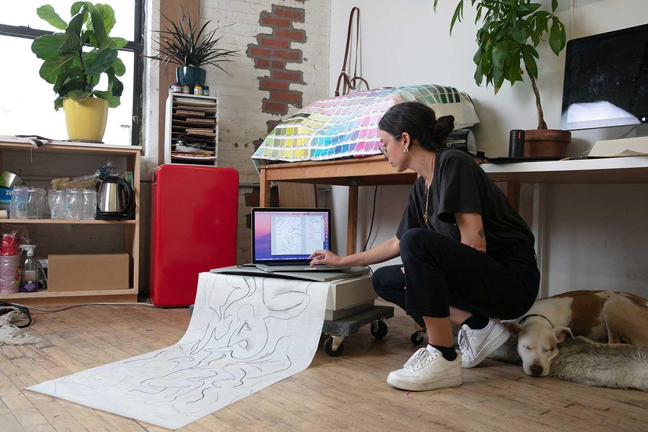 artist on floor scanning large drawing onto computer in studio