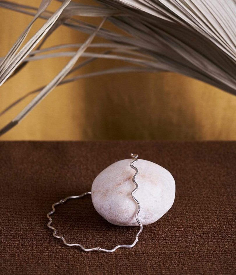 silver necklace draped over a white rock with brown background