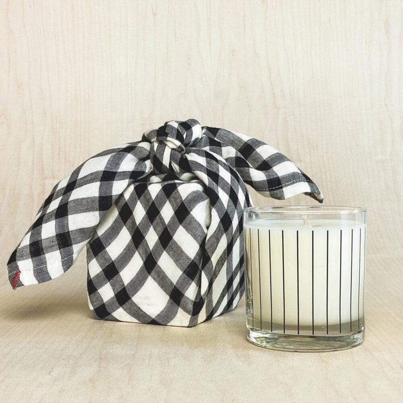 candle in glass container with vertical black stripes and plaid fabric