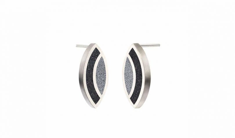 pair of silver stud earrings with black and grey inlays on white background