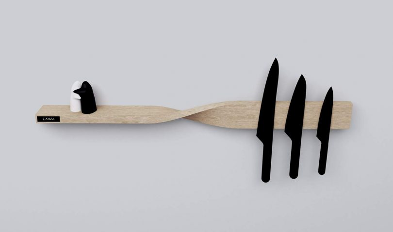 three black knives and salt and pepper shakers attached to and sitting on light wood shelf and magnetic board