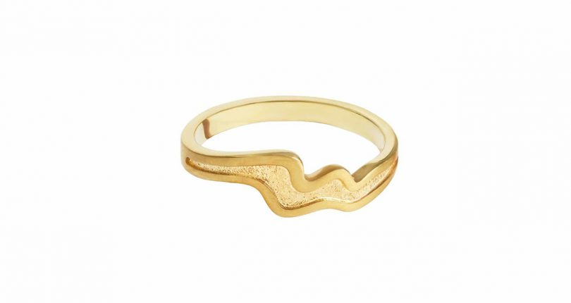 wavy gold ring on white background